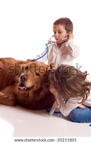 Cute little brother and sister playing veterinary with their dog