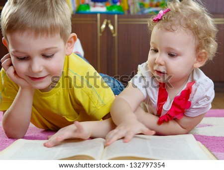 Cute little brother and sister reading book on floor at home