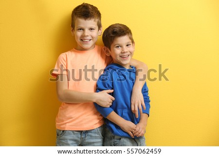 Cute little brothers standing on yellow background Stock foto ©