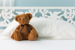Cute little brown teddy bear sitting on the bed