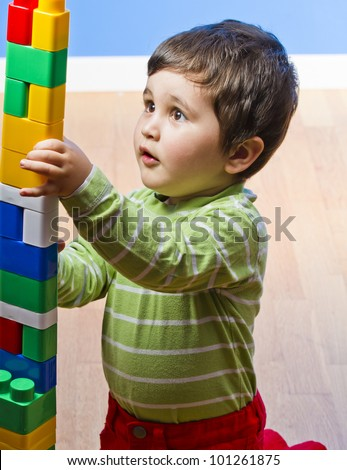 Cute little brunette baby playing with colorful blocks