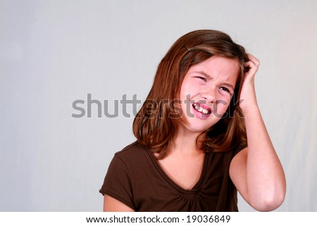 cute little brunette girl scratching her head confused