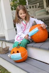 Cute Little Caucasian Girl putting COVID-19 Medical Face Mask PPE on Halloween Pumpkins