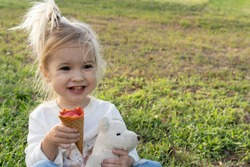 Cute little caucasian kid eating delicious ice cream, smiling, holding white bear toy, green grass at backgound, summer time, copy space.