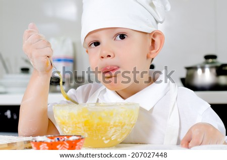 Cute little chef in a white toque and apron tasting his cooking as he mixes ingredients in a bowl looking thoughtfully into the air