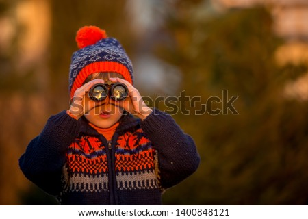 Cute little child, boy, exploring nature with binoculars, looking at sunset