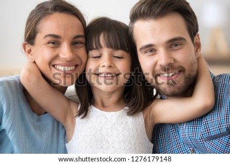 Cute little child daughter embracing caring parents mom and dad looking at camera, preschool kid girl embracing loving mother and father posing together, smiling family of three headshot portrait