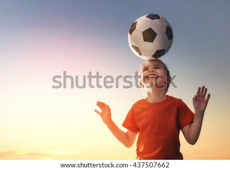 Cute little child dreams of becoming a soccer player. Girl plays football. #437507662