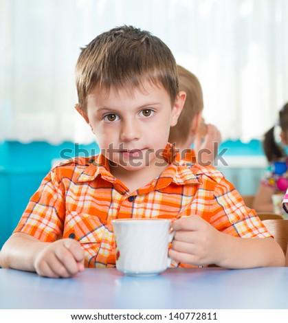 Cute little child drinking milk at kindergarten