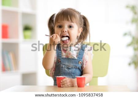 Cute little child girl eating yogurt indoors #1095837458