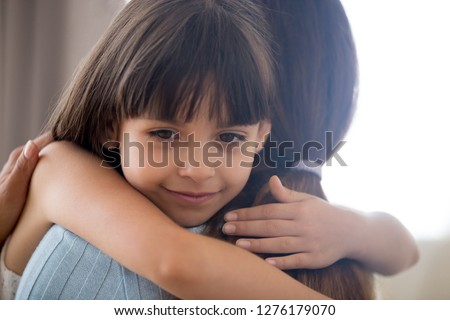 Cute little child girl embracing loving mother, happy kid hugging mom holding tight cuddling, sincere affectionate relationships between mum and daughter, moms love support care or adoption concept