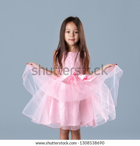 f46358785416 cute little child girl in pink princess dress looking at camera on gray  background. #