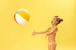 cute little child girl in swimwear playing with beach ball on yellow background