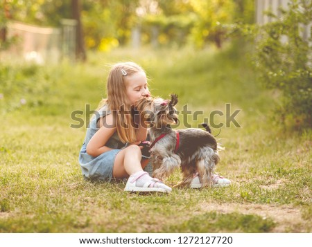 Cute little child girl sitting on the grass with her little Yorkshire terrier dog in the park #1272127720