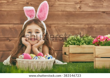 Cute little child girl wearing bunny ears on Easter day. Girl hunts for Easter eggs on the lawn near the house. Girl holding basket with painted eggs. #383146723