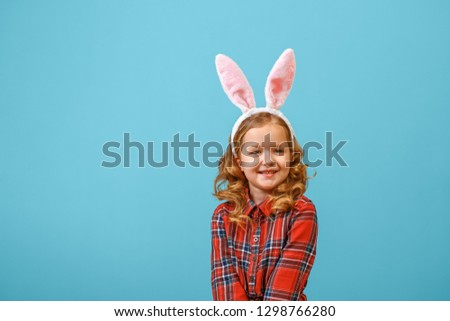 Cute little child girl with bunny ears on a colored background. Happy easter  #1298766280