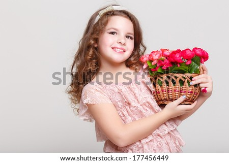 Cute little child girl with spring flowers, happy baby girl with basket of flowers. Isolated in studio on white background.