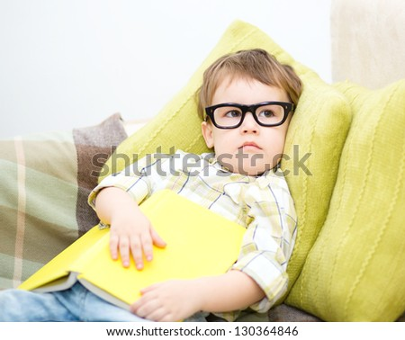 Cute little child holding a book and wearing glasses while laying on couch
