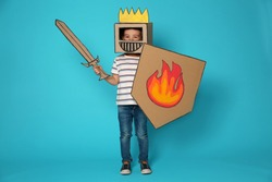 Cute little child in cardboard armor on color background