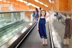 Cute little child in shopping center standing on moving staircase