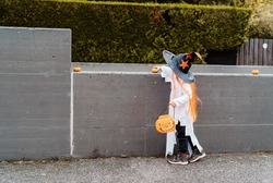 Cute little child in witch hat trick-or-treating on street outdoors with pumpkin bag decorating parking entrance with pumpkins. Kid celebrate traditional Halloween holiday. Trick or treat.