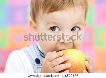 Cute little child is biting red apple and smile, isolated over white