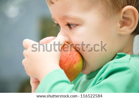 Cute little child is biting red apple and smile while sitting at table, isolated over white