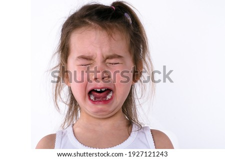 Cute little child is crying on a white background. Сlose-up portrait of a crying baby ストックフォト ©
