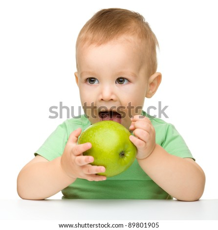 Cute little child is eating green apple while sitting at table, isolated over white