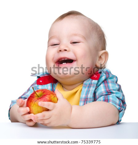 Cute little child is eating red apple and smile while sitting at table, isolated over white