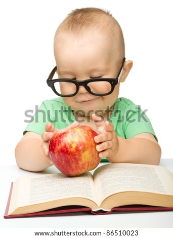 Cute little child is playing with red apple while sitting at table, isolated over white
