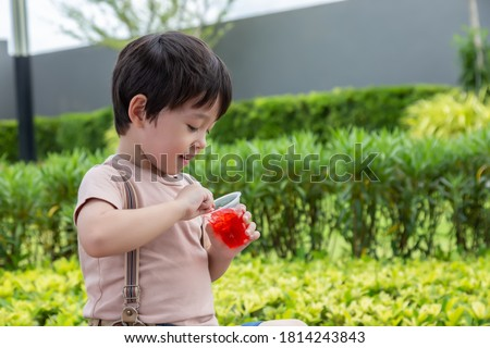 Cute little child love eating sweets or snack. Handsome little boy enjoy eating gelatin or jelly. Adorable kid like eating snack. He feel happy when he eat favorite dessert