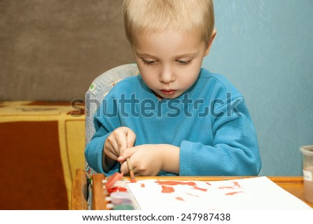 Cute little child painting with colorful paints in home.