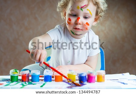 Cute little child painting with paintbrush and colorful paints