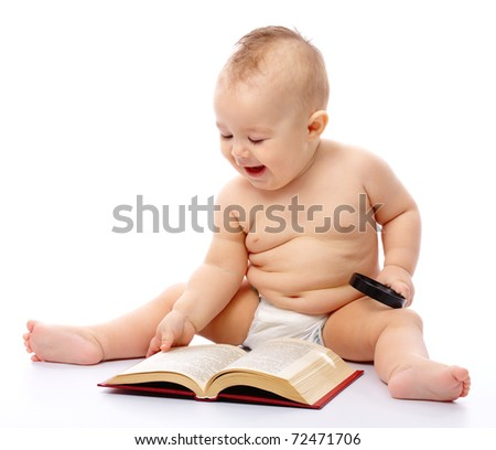 Cute little child play with book and magnifier, isolated over white - stock photo