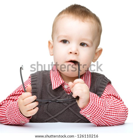 Cute little child play with book while sitting at table and biting glasses, isolated over white