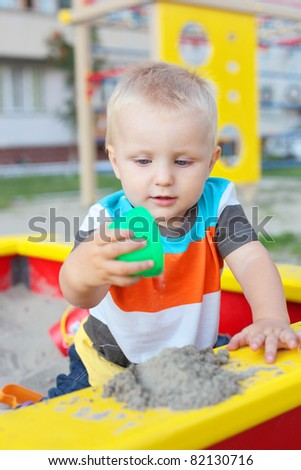 cute little child playing in the sandbox on the playground