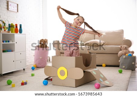 Cute little child playing with cardboard plane at home Imagine de stoc ©