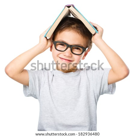 Cute little child plays with book while wearing glasses, isolated over white - stock photo