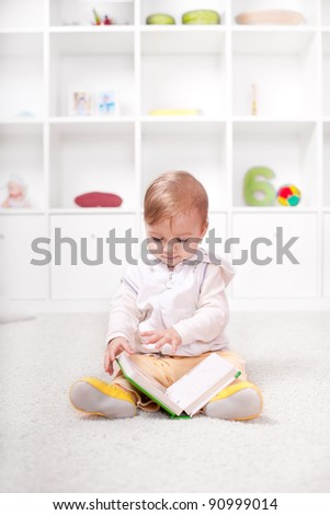 Cute little child reading with curiosity