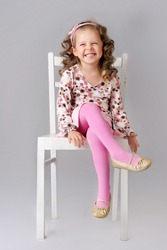 Cute little child sitting on the chair and smiling. wearing pink clothes