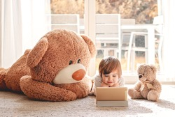 Cute little child watching cartoons on digital tablet device lying on floor with two soft teddy bear toys at home. Modern childhood. Quarantine and isolation period concept. Child alone at home