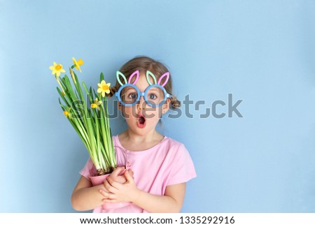 Cute little child wearing bunny ears glasses and holding flowers on Easter day. Easter girl portrait, funny emotions, surprise. Copyspace for text.
