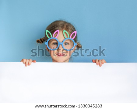 Cute little child wearing bunny ears glasses on Easter day on blue background. Easter girl portrait, funny emotions, surprise. Copyspace for text.