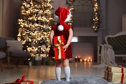 Cute little child wearing Santa hat hiding Christmas gift behind her back at home