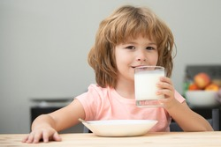 Cute little child with glass of milk at table in kitchen. Kid eating breakfast. Child eating healthy food. Organic milk with calcium. Small child enjoy delicious nutritious lactose free yoghurt.