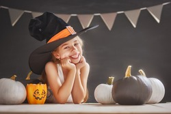 Cute little child with pumpkin. Happy family preparing for Halloween. Girl wearing witch hat.