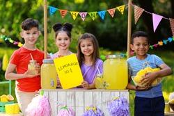 Cute little children at lemonade stand in park. Summer refreshing natural drink