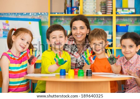 Cute little children drawing with teacher at preschool class