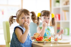 Cute little children eating food at daycare centre